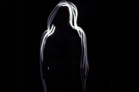 ion: Shadow Girl  A silhouette of a girl on a black background. Glow whitepurple line is around her. Stock Photo
