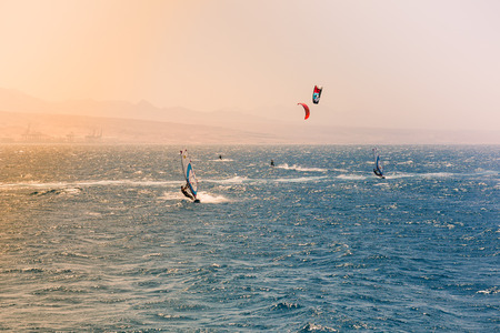 windsurfers: Windsurfers sailing in the Red Sea. Near the beach of Eilat Israel. Bright orange light coming from the sun on the left. Stock Photo