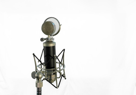 Medium shot of a vocal condenser microphone with wind screen isolated on white background. Stock Photo