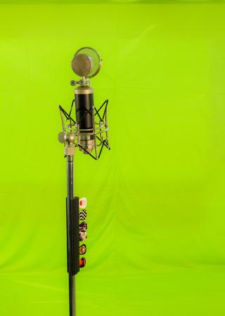 long shot: Campo lungo di un microfono a condensatore vocale con schermo vento isolato su sfondo verde. Cinque plettri illustrati collegati al sul cavalletto.
