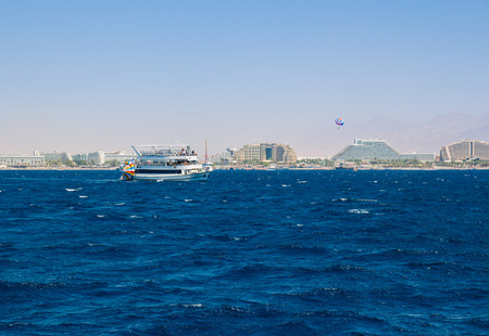 eilat: Yacht sailing in the Red Sea. In the background the hotel strip of Eilat.
