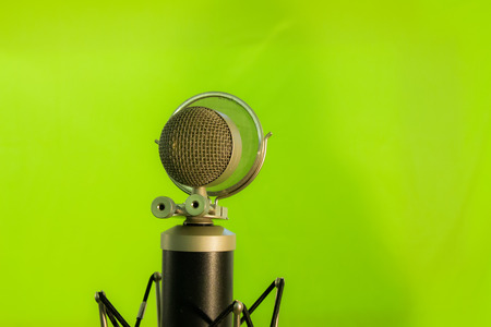 condenser: Close up of a vocal condenser microphone with wind screen isolated on green background.