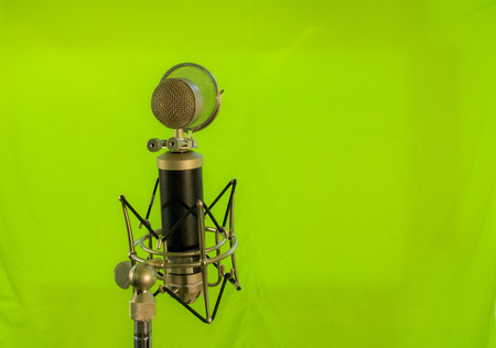 condenser: Medium shot of a vocal condenser microphone with wind screen isolated on green background.
