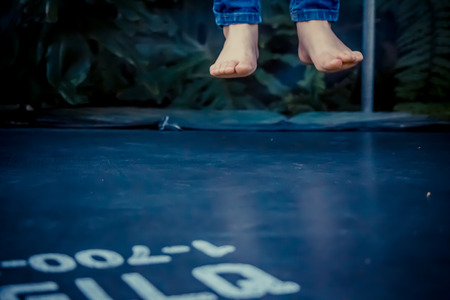 levitating: Legs floating in the air after jumping on the trampoline. Stock Photo