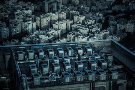 Industrial city. Aerial view of a roof of a building which there are many air conditioners and pipes. In the background there are white residential houses. Cold atmosphere. Stock Photo