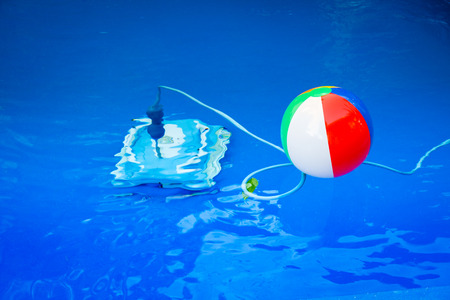Colorful beach ball floating in pool and next to him underwater a cleaning robot