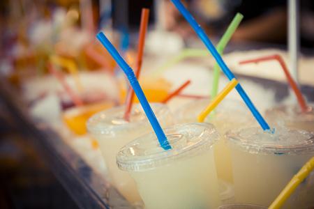 alimentos y bebidas: Selecci�n de vasos de pl�stico con zumo de pomelo y pajitas de colores, en rojo, amarillo, azul y verde. Cierre y foco selectivo Foto de archivo