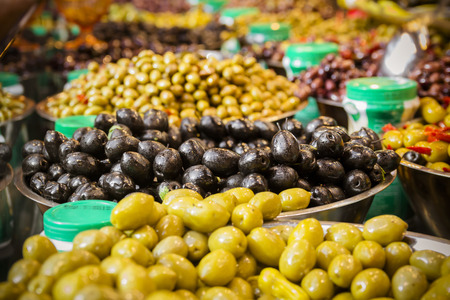olive green: Olives at a market stall. A variety of types of olives. Green, black, Syrians and others. Stock Photo