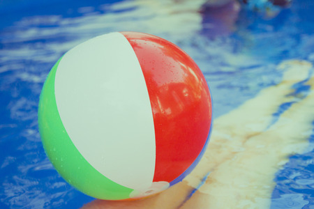 children party: Colorful beach balls floating in pool. A womans legs in the water