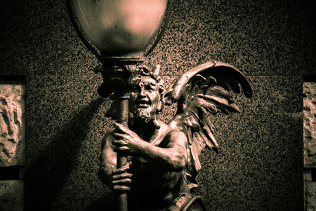 angel statue: Statue of a demon holding a lamppost
