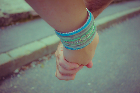 young style: Couple holding hands. Vintage look. close up.