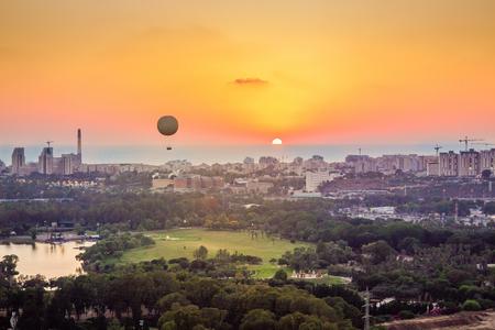 Skyline van Tel Aviv bij zonsondergang. Kan een heteluchtballon in de lucht zien vliegen. Daarnaast kunt u de wijk in het noorden van Tel Aviv, Hayarkon Park, Reading Power Station en de Middellandse Zee zien. Stockfoto