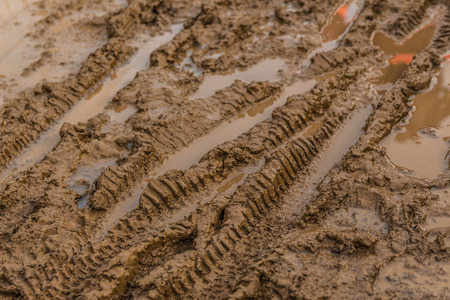 Texture of wet brown mud with bicycle tyre tracks
