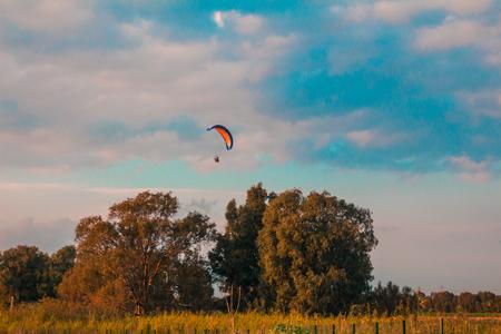 motorizado: parapente motorizado volando en zona rural durante la puesta del sol