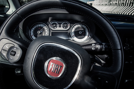 fiat: Alberobello, Italy - August 2: Close up of Fiat 500L steering wheel and dashboard on August 2, 2014.