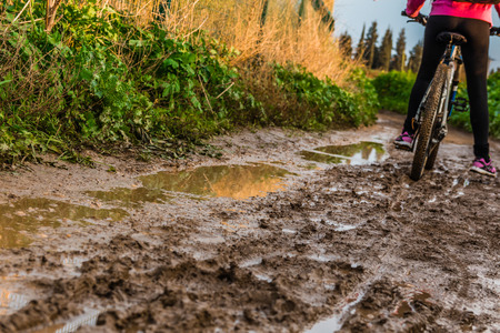 mountainbiking: Bicycle ride through muddy dirt road