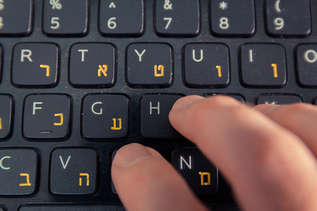 hebrew letters: Man typing on a keyboard with letters in Hebrew and English - Laptop keyboard - Top View - Close up