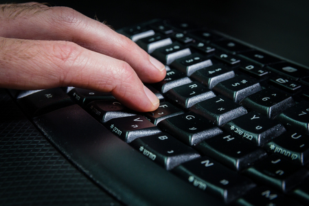 hebrew: Man typing on a keyboard with letters in Hebrew and English - Wireless keyboard - Dark atmosphere