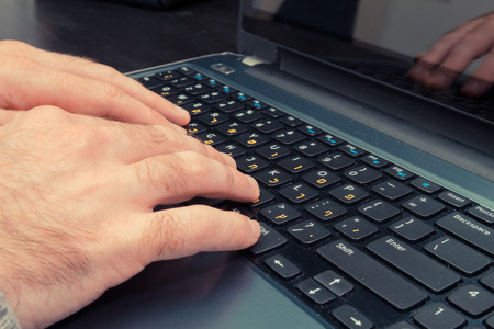 hebrew letters: Man typing on a keyboard with letters in Hebrew and English - Laptop keyboard Stock Photo