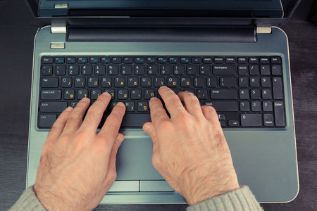 hebrew letters: Man typing on a keyboard with letters in Hebrew and English - Laptop keyboard - Top View