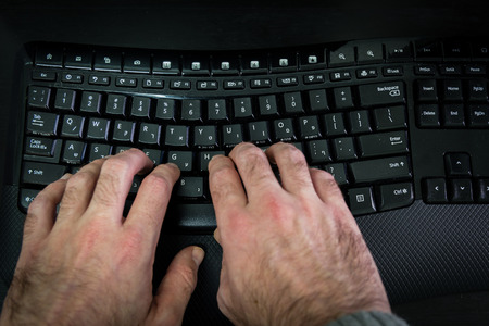hebrew letters: Man typing on a keyboard with letters in Hebrew and English - Wireless keyboard - Top View - Dark atmosphere