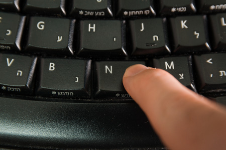 hebrew letters: Man typing on a Wireless keyboard with letters in Hebrew and English - Press the New button  - Top View