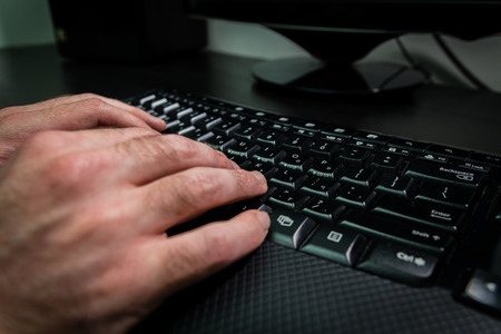english letters: Man typing on a keyboard with letters in Hebrew and English - Wireless keyboard - Dark atmosphere