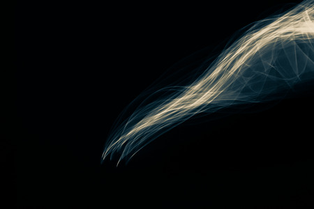 strobe light: Light painted glowing abstract blue and yellow curved lines on a black background