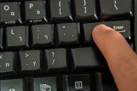tecla enter: Hombre escribiendo en un teclado inalámbrico con letras en hebreo y en Inglés - pulse la tecla Intro - Vista superior Foto de archivo