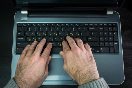 hebrew letters: Man typing on a keyboard with letters in Hebrew and English - Laptop keyboard - Top View - Dark atmosphere