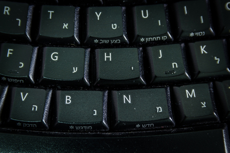 english letters: Keyboard with letters in Hebrew and English - Wireless keyboard - Top View - Close up - Dark atmosphere Stock Photo