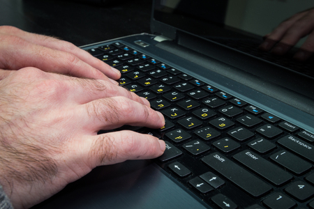 hebrew letters: Man typing on a keyboard with letters in Hebrew and English - Laptop keyboardDark atmosphere