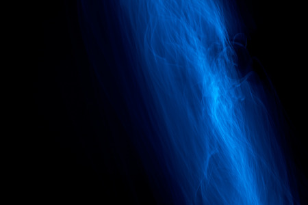 strobe light: Light painted glowing abstract blue curved lines on a black background