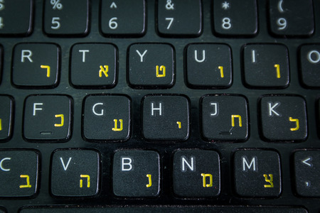 english letters: Keyboard with letters in Hebrew and English - Laptop keyboard - Top View - Close up - Dark atmosphere Stock Photo