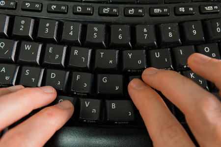 hebrew letters: Man typing on a keyboard with letters in Hebrew and English - Wireless keyboard - Top View Stock Photo