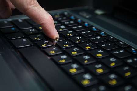 hebrew: Man typing on a keyboard with letters in Hebrew and English - Laptop keyboard - Close upDark atmosphere