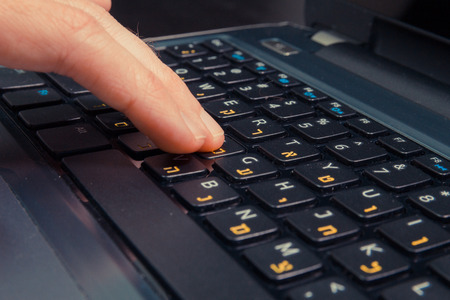 hebrew letters: Man typing on a keyboard with letters in Hebrew and English - Laptop keyboard - Close up