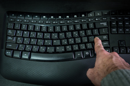 enter key: Man typing on a Wireless keyboard with letters in Hebrew and English - Press the Enter key - Top View - Dark atmosphere