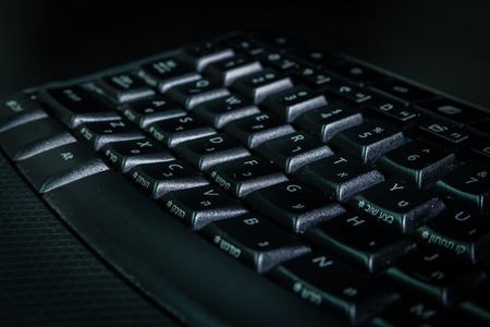 english letters: Keyboard with letters in Hebrew and English - Wireless keyboard - Close up - Dark atmosphere