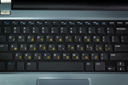 hebrew letters: Keyboard with letters in Hebrew and English - Laptop keyboard - Top View -  Dark atmosphere