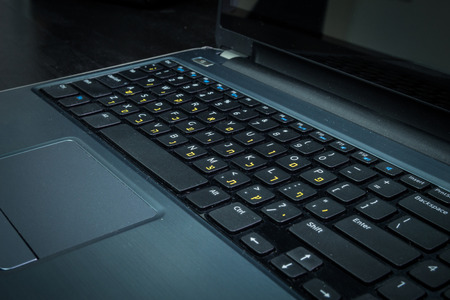 hebrew letters: Keyboard with letters in Hebrew and English - Laptop keyboard - Dark atmosphere Stock Photo