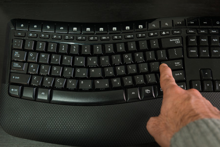 hebrew letters: Man typing on a Wireless keyboard with letters in Hebrew and English - Press the Enter key - Top View Stock Photo