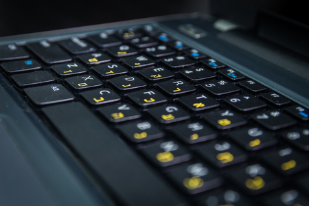 hebrew letters: Keyboard with letters in Hebrew and English - Laptop keyboard - Close up - Dark atmosphere