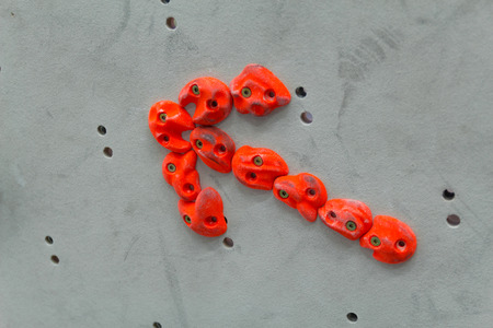 holds: Red climbing holds in the shape of an arrow on grey wall
