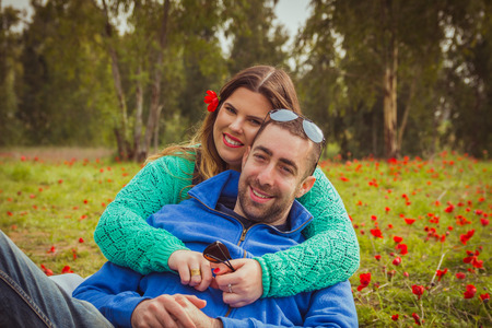 girl sitting: Young couple sitting on the grass in a field of red poppies and smiling at the camera. Stock Photo