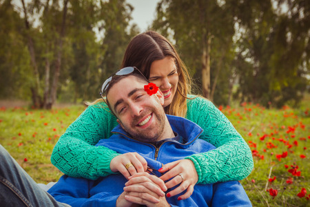 ni�o y ni�a: Young couple sitting on the grass in a field of red poppies and smiling and laughing at each other