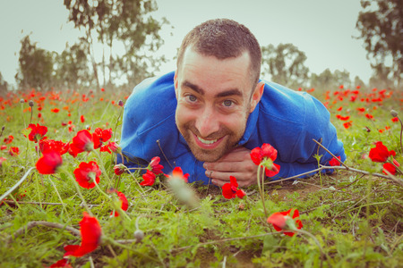 25 29: Young man lying on the grass in a field of red poppies and smiling at the camera