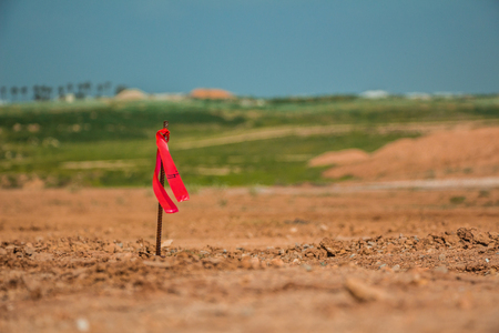 benchmarks: Metal survey peg with red flag on construction site. Stock Photo