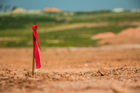 topographical: Metal survey peg with red flag on construction site. Stock Photo