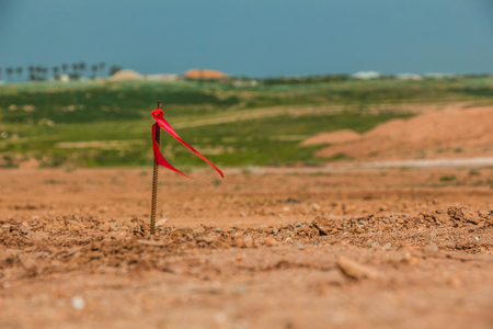 Metal survey peg with red flag on construction site Archivio Fotografico